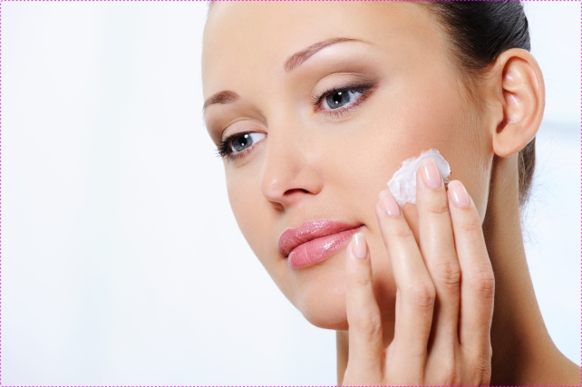 woman caring of her face with moisturizer cream